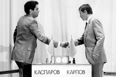 Chess masters Gary Kasparov and Anatoly Karpov shake hands before an earlier match.  The two masters are playing a 12-game exhibition series on the 25th anniversary of their first contest.