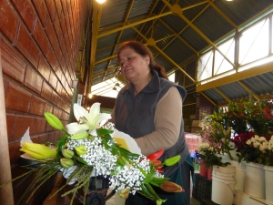 Senora Gloria building a flower bouquet at Mercado Providencia.