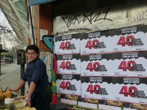 A sopaipilla salesman in front of posters for an artist performance.