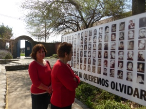 Two women look at a gallery of victims at Villa Grimaldi.