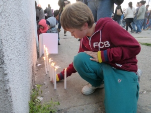 A child lights a candle at the Estadio Nacional.