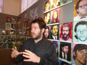 Emilio stands in front of artwork of victims' faces done by Brian Carlson.
