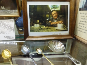 A picture and three spoons inside a glass case at Cafe Tortoni.