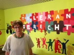 Principal Elvira Bluemel stands in front of the mural at Realschule Uberruhr.