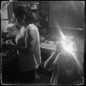 Pamela Betancur and her son Juan Jose Larraguibel in the kitchen of their house in a campamento, or shantytown, in the La Florida neighborhood in Santiago. Jon Lowenstein/NOOR/Pulitzer Center on Crisis Reporting